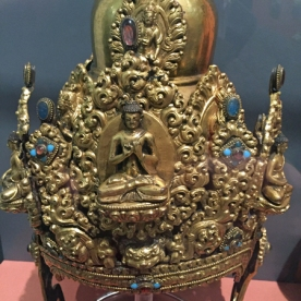 This crown has individually cast medallions depicting Bodhisattvas positioned around the dome, with Vairocana in the centre; each is framed within an elaborate foliate medallion.